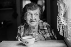 Un retrato feliz mayor de la mujer en la tabla con una taza de té Fotografía de archivo libre de regalías