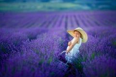 Un retrato hermoso del aire libre de la chica joven ni?o en sombrero con las flores de cesta que cosechan en el campo Provence de fotos de archivo