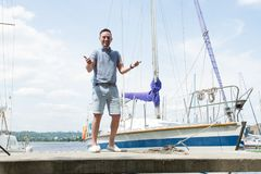 Un retrato sonriente del dueño de un yate en el embarcadero con ambos pulgares para arriba río y yates en fondo Marinero acertado fotos de archivo libres de regalías