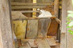 Un retrete de madera viejo en un campo de la explotación minera en el Yukón Imágenes de archivo libres de regalías