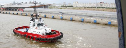 Un rimorchiatore lotta per tirare una nave dal bacino fotografia stock