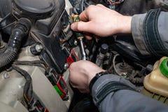 Un riparatore dell'automobile svita si separa una chiave con una maniglia verde nel suh del compartimento di motore come le cande fotografie stock libere da diritti