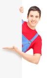 Un riparatore sorridente che mostra su un pannello in bianco Fotografia Stock Libera da Diritti