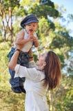 Figlio di sollevamento del bambino della mamma allegra su nella risata dell'aria Immagini Stock