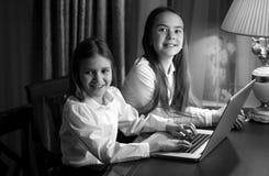 Un ritratto in bianco e nero di due sorelle che per mezzo del computer portatile Immagine Stock Libera da Diritti
