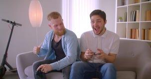 Un ritratto del primo piano di due uomini caucasici bei adulti che giocano i video giochi con l'eccitazione che si siede sullo st stock footage