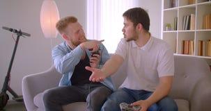 Un ritratto del primo piano di due uomini caucasici bei adulti che giocano i video giochi divertendosi seduta sullo strato all'in video d archivio