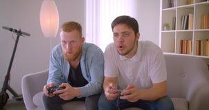 Un ritratto del primo piano di due uomini caucasici bei adulti che giocano i video giochi che si siedono sul sofà all'interno Vin video d archivio