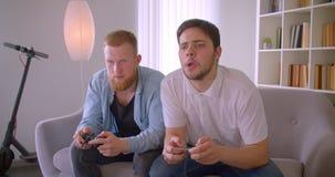 Un ritratto del primo piano di due uomini caucasici bei adulti che giocano i video giochi che si siedono sullo strato all'interno stock footage