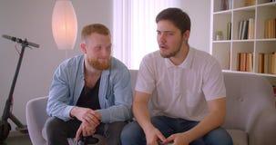 Un ritratto del primo piano di due uomini caucasici felici adulti che giocano i video giochi che si siedono sullo strato all'inte video d archivio