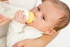 Un ritratto del primo piano di 3 mesi del neonato della bottiglia del holdin con latte ed il cibo Fotografie Stock