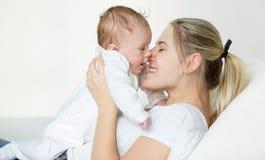 Un ritratto del primo piano di 3 mesi del neonato e della madre sorridente divertendosi sul letto Fotografie Stock Libere da Diritti