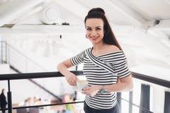 Un ritratto del primo piano di una donna con il sorriso perfetto che tiene una tazza di cappuccino o di caffè Denti bianchi e tru fotografie stock