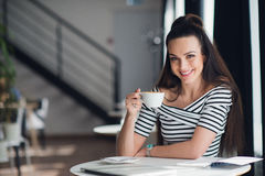Un ritratto del primo piano di una donna con il sorriso perfetto che tiene una tazza di cappuccino o di caffè Denti bianchi e tru Immagini Stock