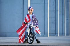 Un ritratto del ragazzo americano che si siede sulla bici ha avvolto la bandiera americana Immagini Stock