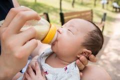Un ritratto del ragazzo di neonato coreano che è alimentato da suo padre che per mezzo del biberon immagini stock