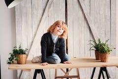 Un ritratto dell'interno di 5 anni del ragazzo con capelli lunghi che si siedono sulla tavola Immagine Stock
