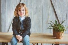 Un ritratto dell'interno di 5 anni del ragazzo con capelli lunghi che si siedono sulla tavola Fotografia Stock