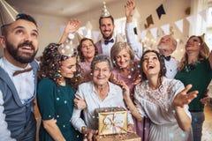 Un ritratto della famiglia di diverse generazioni con i presente su una festa di compleanno dell'interno immagine stock libera da diritti