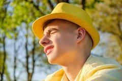 Un ritratto di un adolescente felice fuori, portando una camicia e un cappello gialli contro un cielo blu, albero verde fotografia stock