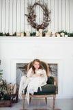 Un ritratto di 7 anni del bambino del libro di lettura a casa su natale Fotografia Stock