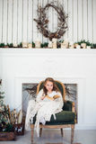 Un ritratto di 7 anni del bambino del libro di lettura a casa su natale Immagine Stock