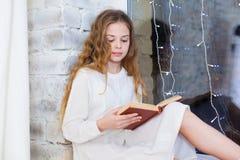 Un ritratto di 10 anni del bambino del libro di lettura sulla finestra su natale Fotografia Stock