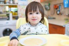Un ritratto di 2 anni di piccolo bambino che mangia il porridge del grano con la pompa Immagine Stock