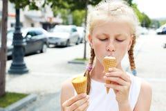 Un ritratto di 7 anni scherza la ragazza che mangia il gelato saporito in città Fotografia Stock