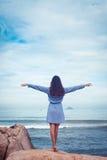 Un ritratto di bella donna asiatica in vestito indietro sta, mani ai lati su una pietra dal mare Immagine Stock