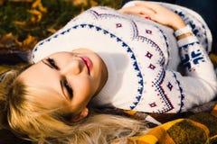 Un ritratto di bella ragazza mette su un plaid in autunno Fotografia Stock