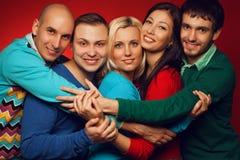 Un ritratto di cinque amici intimi alla moda che abbracciano, sorridenti e posi Immagini Stock