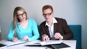 Un ritratto di due alla moda casuali, del ragazzo e della ragazza dei riusciti studenti nel corridoio della lettura delle bibliot stock footage