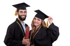 Un ritratto di due allievi di laurea felici Isolato sopra fondo bianco Immagini Stock