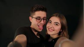 Un ritratto di due amanti felici che fanno selfie sullo smartphone su fondo nero video d archivio