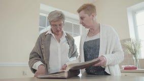 Un ritratto di due amiche adulte che considerano un album di foto Donna anziana con capelli bianchi e vetri e un'amica archivi video