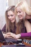 Un ritratto di due amiche caucasiche emozionali con il computer portatile divertendosi all'interno fotografie stock