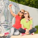 Un ritratto di due amici di adolescenti in attrezzatura dei pantaloni a vita bassa che ha f immagine stock