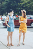 Un ritratto di due amici unformal caucasici bianchi degli adolescenti degli studenti dei pantaloni a vita bassa delle ragazze Fotografia Stock