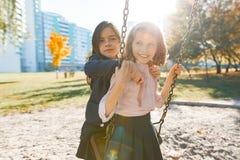 Un ritratto di due bambini delle ragazze che abbracciano e che oscillano in un parco soleggiato di autunno, ora dorata immagini stock libere da diritti