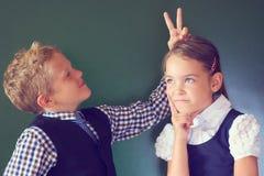 Un ritratto di due bei bambini ragazzo e ragazza dell'europeo in uniforme scolastico che sta accanto alla lavagna Il ragazzo most fotografia stock libera da diritti