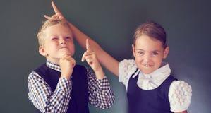 Un ritratto di due bei bambini ragazzo e ragazza dell'europeo in uniforme scolastico che sta accanto alla lavagna La ragazza most fotografia stock libera da diritti