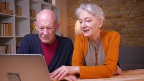 Un ritratto di due coniugi caucasici dai capelli grigi senior che parlano nel videochat che si accarezza tenero nell'ufficio archivi video