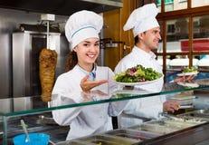 Un ritratto di due cuochi unici ospitali con il kebab al posto di pasto rapido Fotografia Stock