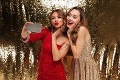 Un ritratto di due donne abbastanza adorabili in vestiti frizzanti Fotografia Stock