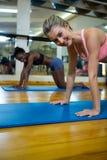 Un ritratto di due donne adatte che fanno allungando esercizio sulla stuoia Immagini Stock