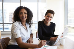 Un ritratto di due donne di affari con il computer portatile in ufficio fotografia stock libera da diritti