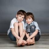 Un ritratto di due fratelli felici su fondo agray Fotografie Stock