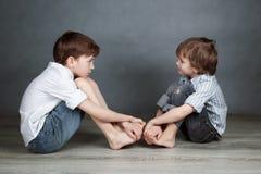 Un ritratto di due fratelli felici su fondo agray Fotografia Stock Libera da Diritti