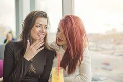 Un ritratto di due giovani belle donne alla caffetteria, conversazione della ragazza Fotografie Stock